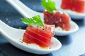Macro close up of tuna morsel extreme appetizing on white ceramic spoon Stock Photography