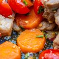 Macro of fried slices of carrots, tomatoes, garlic, green onions and spices with small pieces of meat. Shallow depth of Royalty Free Stock Photo