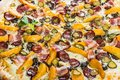 Macro. Huge pizza with sausage, pickled cucumber, bacon Royalty Free Stock Photo