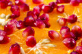 Macro peeled ripe pomegranate fruit with many slices of orange f