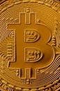 Macro photography of a golden yellow metal bitcoin. Close up shiny metal texture. Abstract business and modern technology backgro Royalty Free Stock Photo