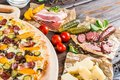 Macro. Pizza with sausage, pickled cucumber, bacon on a round cu Royalty Free Stock Photo