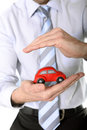 Macro red toy car in businessman hand close up of a the hands of a business man wearing a blue shirt and blue tie on a white Stock Photo