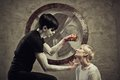 Mad games scary guy in black with apple and girl in white in a cell of an asylum Stock Photos