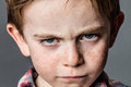 Mad little kid with furious blue eyes for childhood rebellion Royalty Free Stock Photo