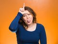 Mad pissed off woman showing loser sign closeup portrait angry sticking tongue out hand on forehead isolated orange background Royalty Free Stock Photo