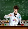 Mad professor pours some liquid in beaker Stock Images