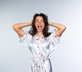 Mad woman in peignoir early morning on grey background Royalty Free Stock Photography