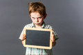 Mad young kid with empty writing slate for sulking attitude Royalty Free Stock Photo