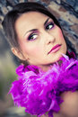 Made for magenta beautiful brunette model wearing make up with a purple feathered scarf leaning against a tree looking over her Royalty Free Stock Photos