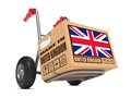 Made in uk cardboard box on hand truck with flag of united kingdom and united kingdom slogan white background free shipping Royalty Free Stock Images