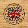 Made in the uk stamp on wooden background vector with flag of gb circular lettering Royalty Free Stock Image