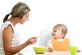 Madre spoon-feeding su bebé divertido Foto de archivo