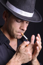 Mafia smoker close up portrait of man smoking cigarrette on dark background Royalty Free Stock Photography