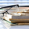 Magazines stack of with glasses in front of a window Royalty Free Stock Images
