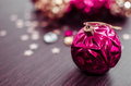 Magenta christmas ball on bokeh background of xmas ornaments. Royalty Free Stock Photo
