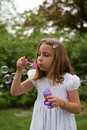 Maggiebubblesredone little girl blowing bubbles with a white dress in summer Stock Photo