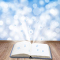 Magic book open on wooden planks with light and letters Royalty Free Stock Images