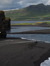 Magic iceland landscape with black lava sand and green eroded hills Royalty Free Stock Photo