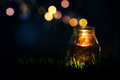 Magic jar glass in the grass at night with lights flying around Royalty Free Stock Photos