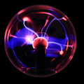 Magic rays plasma ball souvenir with magenta blue lightnings isolated on a black background Royalty Free Stock Images