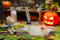 Magic scrolls pumpkins and candles in the witch s house on wooden background Royalty Free Stock Images