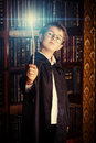 Magic wand a boy stands with in the library by the bookshelves with many old books fairy tales vintage style Royalty Free Stock Photos