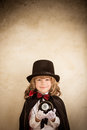 Magician child holding magic ball against grunge wall background Stock Photos