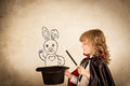 Magician child holding a top hat with drawn rabbit against grunge background focus on the hat Royalty Free Stock Images