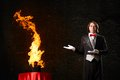 Magician conjures a stream of fire out of the hat Stock Image