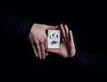 Magician hands close up of holding joker playing card showing his trick with cards on black background Royalty Free Stock Photography