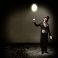 Magician holding a glowing balloon in top hat and tie baloon and staring at him Royalty Free Stock Image