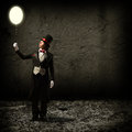 Magician holding a glowing balloon in top hat and tie baloon and staring at him Stock Photo