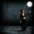 Magician keeps the moon on a string in top hat and tie holding glowing Stock Photo