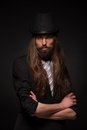 Magician portrait of handsome performing black magic long haired bearded man with his arms crossed Stock Photography