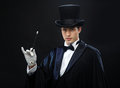 Magician in top hat with magic wand showing trick performance circus show concept Stock Photo
