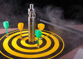Magnetic dart arrows and electronic cigarette within vapor on yellow dart board. Royalty Free Stock Photo