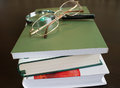 Magnifying glass and glasses on books a dark brown table Stock Image