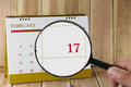 Magnifying glass in hand on calendar you can look seventeenth Royalty Free Stock Photo