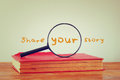 Magnifying glass , old book with the phrase share your story. filtered image.