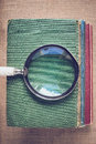Magnifying glass with old books on vintage background with insta burlap instagram style filter Stock Photos