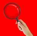 Magnifying glass on red background hand holding Stock Photo