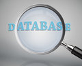 Magnifying glass showing database word on grey background Royalty Free Stock Image