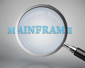 Magnifying glass showing mainframe word on grey background Stock Photography