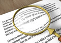 Magnifying glass on a wooden table increases the text about finance Stock Images