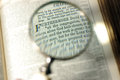 Magnifying the text on a bible an old page Royalty Free Stock Photos