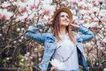 Magnolia. girl or cute woman near blossoming, magnolia flowers tree in spring park on spring sunny day Royalty Free Stock Photo