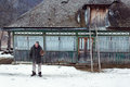 MAGURA, ROMANIA - 05 FEB: Old romanian peasant in front of his old house on February 05 2015. Magura is a village in Carpatian