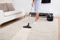 Maid cleaning carpet with vacuum cleaner cropped image of young at home Royalty Free Stock Photography