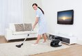 Maid cleaning carpet with vacuum cleaner Royalty Free Stock Photo